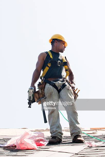 roofer with nail gun putting shingles on roof of new home - safety harness stock pictures, royalty-free photos & images