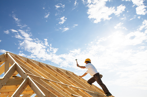 roofer worker builder working on roof structure at construction site 908264580