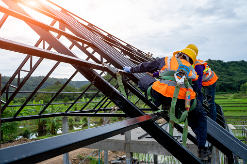 Roofer worker in protective uniform wear and gloves 1171642458