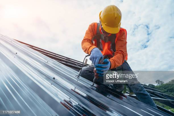roofer worker in special protective work wear and gloves. - industrie du bâtiment photos et images de collection