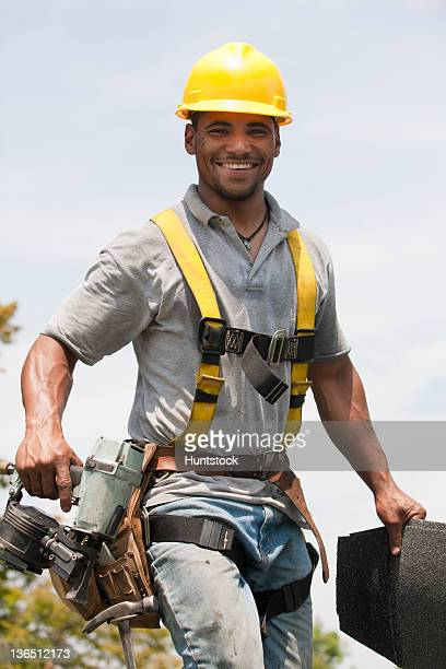 roofer working on shingling a new roof - safety harness stock photos and pictures