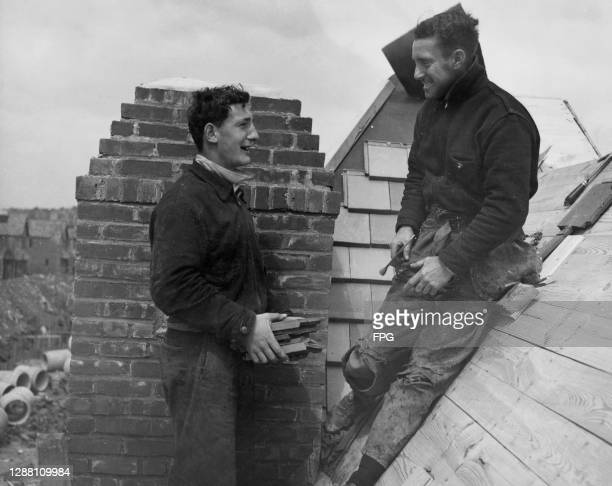 Roofers in conversation atop a building on a pitched roof on a construction site, with sections of drainage pipes in the bottom left-hand corner of...