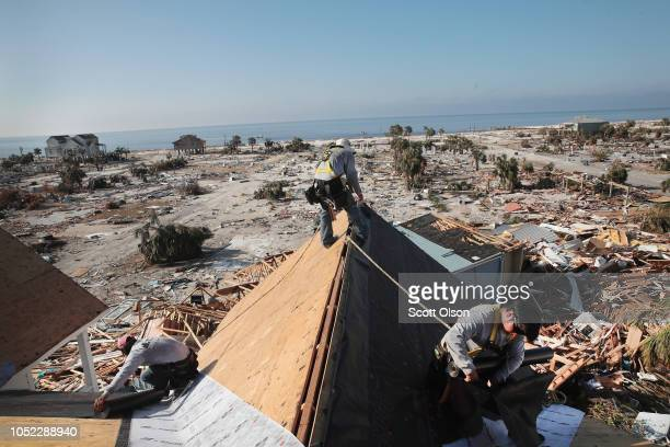 Roofers work to replace the roof on a townhome after it was damaged by Hurricane Michael on October 16 2018 in Mexico Beach Florida The neighborhood...