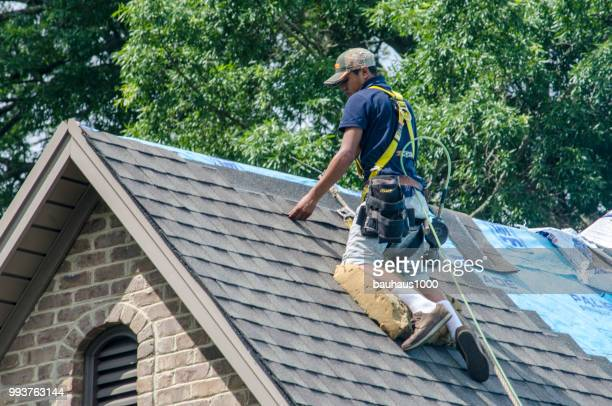 roofing contractors replacing damaged roofs after a hail storm - roof stock pictures, royalty-free photos & images