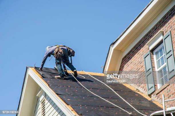 roofing contractors replacing damages roofs after a hail storm - roof stock pictures, royalty-free photos & images
