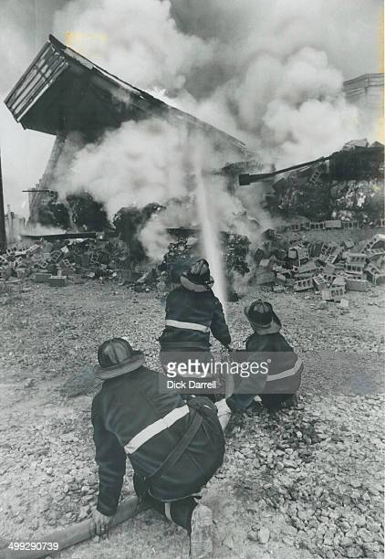 Roof's down Toronto firemen aim water at bales of paper after fire and heat brought down the roof last night at Levis Paper Ltd recycling plant on...