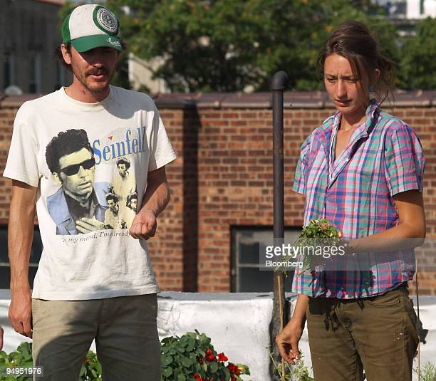 Rooftop farmers Ben Flanner left and Annie Novak work on their farm in Brooklyn New York US on July 14 2009 The farmers sell produce to local...