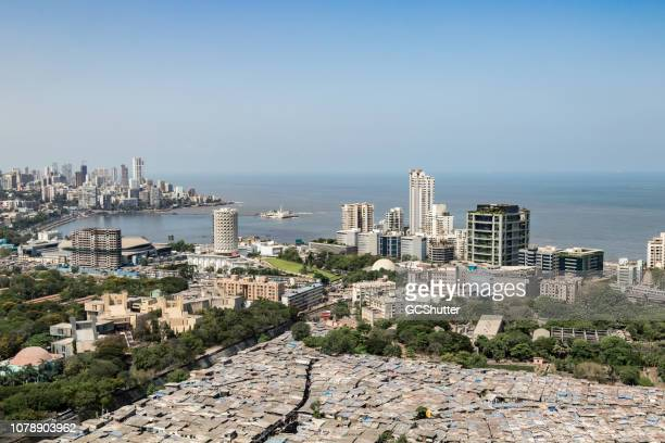 rooftop image of slums, buildings and neighboring community - mumbai, maharashtra - mumbai stock photos and pictures