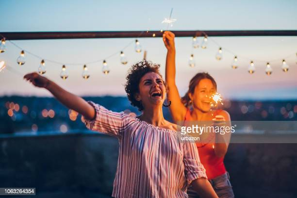 rooftop party friends with sparklers - terraced field stock pictures, royalty-free photos & images