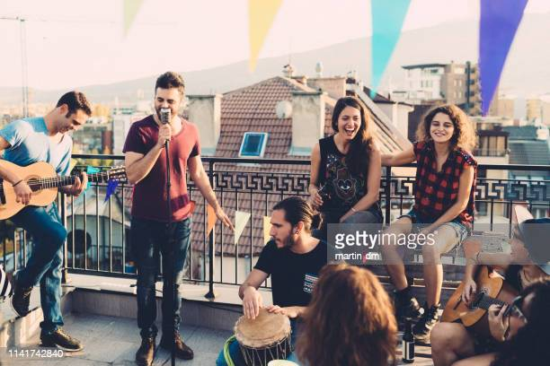 rooftop party with live music - performance group stock pictures, royalty-free photos & images