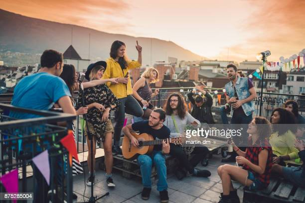 rooftop party with live music - martin guitar stock photos and pictures