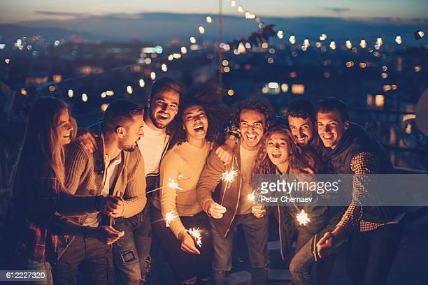Rooftop party with sparklers at night