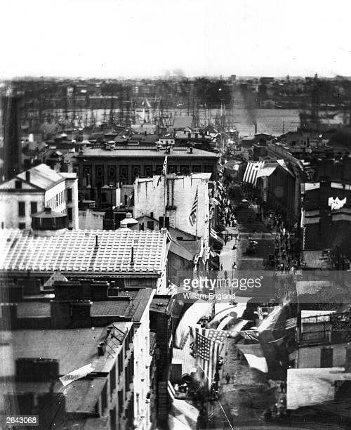 Roof-top view of Wall Street, New York City, looking east from Trinity Church, with the East River docks in the distance. Built in 1846, Trinity...