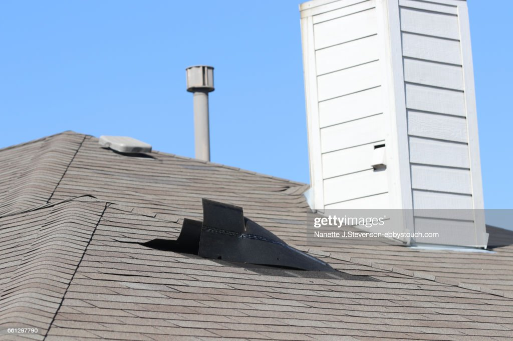Rooftop with wind damage to shingles : Stock Photo