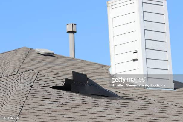 rooftop with wind damage to shingles - nanette j stevenson stock photos and pictures