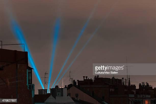 Rooftops and blue laser lights at sunset, Barcelona, Spain