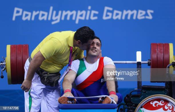 Roohallah Rostami of Iran receives a kiss from his coach after a successful lift in the Men's 675kg competition on day 4 of the London 2012...