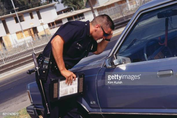 lapd rookie checking registration sticker on automobile - los angeles police department stock pictures, royalty-free photos & images