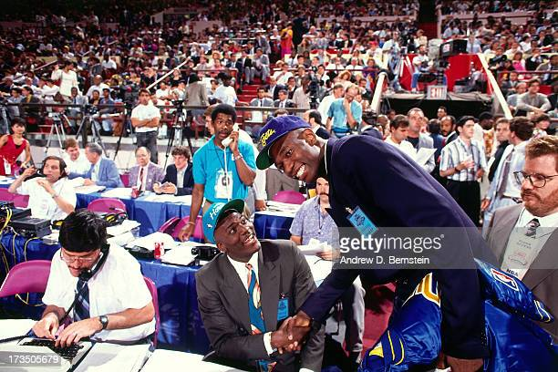Rookie Larry Johnson of the Charlotte Hornets congratulates Dikembe Mutombo of the Denver Nuggets during the 1991 NBA Draft at Madison Square Garden...