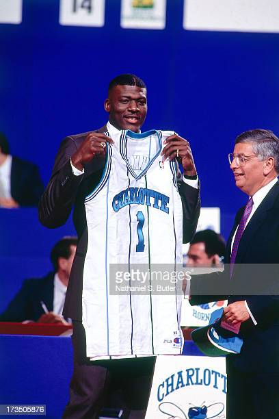 Rookie Larry Johnson of the Charlotte Hornets holds up a jersey next to Commissioner David Stern during the 1991 NBA Draft at Madison Square Garden...
