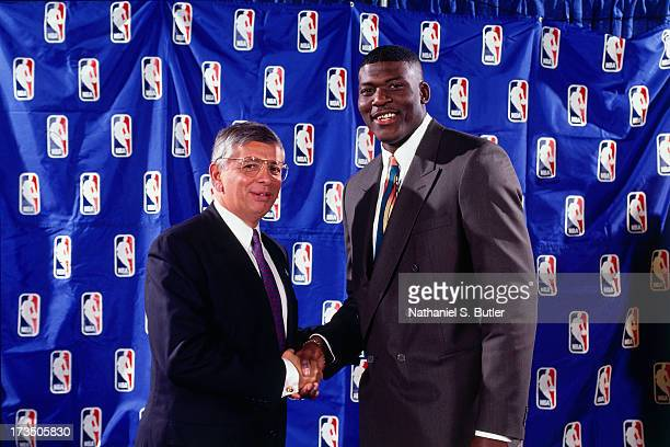 Rookie Larry Johnson of the Charlotte Hornets shakes hands with Commissioner David Stern of the NBA during the 1991 NBA Draft at Madison Square...