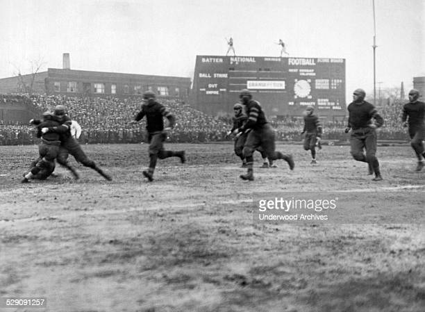 Rookie Red Grange getting tackled at Cub's Park in his first professional game for the Chicago Bears playing against their Southside rivals the...