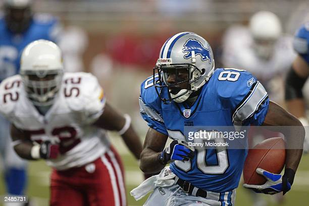 Rookie wide receiver Charles Rogers of the Detroit Lions runs the ball as linebacker Levar Fisher of the Arizona Cardinals tries to catch Rogers at...
