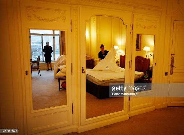 A room attendant is reflected in mirrors as she changes bedding in the Monet Suite at the Savoy Hotel on December 6 2007 in London Some of the...