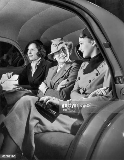 Three elegant ladies demonstrate the roomy width of the 1937 Willys Sedan.