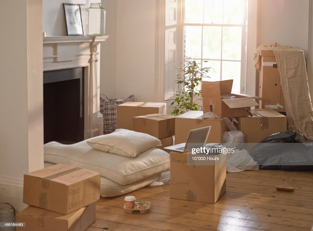 A room full of packing boxes and a laptop : Stock Photo