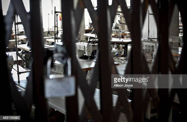 A room of sewing machines is locked behind a metal gate at a Tuba Group factory August 4 2014 in Dhaka Bangladesh Garment workers have been on a...