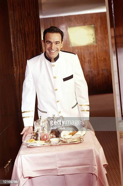 Room service waiter wheeling in tray of food