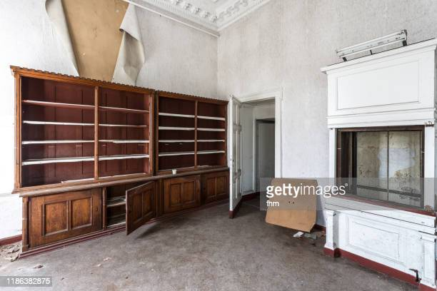 room with furnitures in an abandoned building - distruzione foto e immagini stock