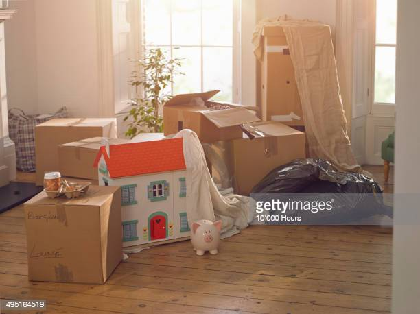 Room with packing boxes dolls house and piggybank