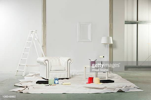 Room with paint pots and white armchair