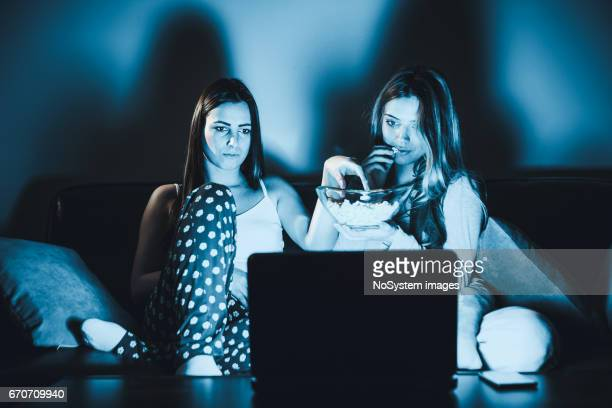 Roommates, lesbian couple watching movie on laptop at home in livingroom.