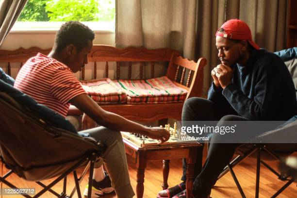 roommates playing chess during self-isolation - webfluential stock pictures, royalty-free photos & images