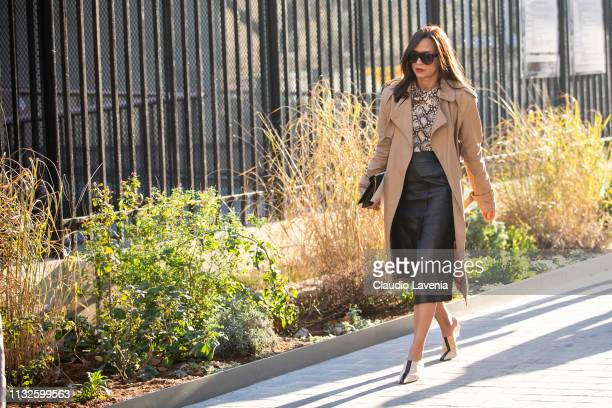 Roopal Patel wearing a snake print shirt black midi leather skirt beige trench coat beige and black mules and black bag is seen outside Lanvin on Day...