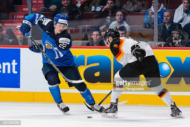Roope Hintz of Team Finland plays the puck around Patrick Kurz of Team Germany in a preliminary round game during the 2015 IIHF World Junior Hockey...