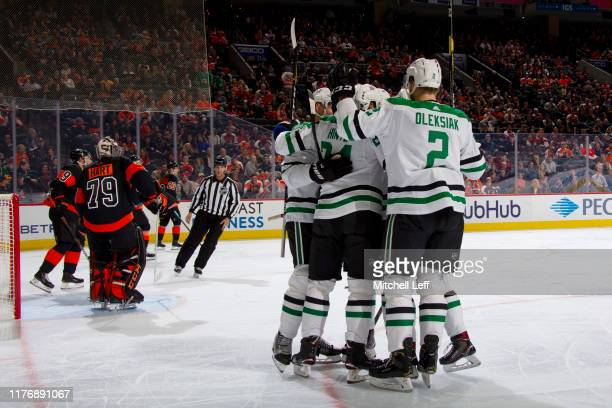 Roope Hintz of the Dallas Stars celebrates with Jamie Oleksiak and the rest his teammates in front of Carter Hart of the Philadelphia Flyers after...