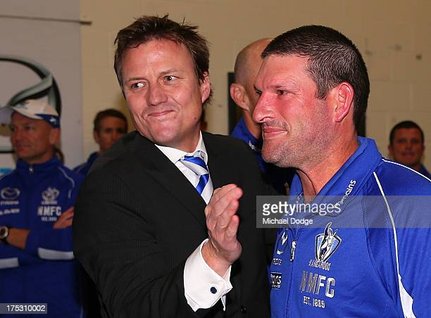 Roos President James Brayshaw and assistant coach Brett Allison celebrate their win during the round 19 AFL match between the North Melbourne...