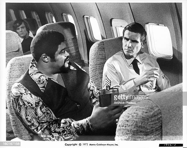Roosevelt Grier and James Brolin sitting next to each other on a plane in a scene from the film 'Skyjacked' 1972