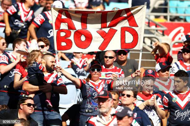 A rooster supporter holds up a banner during the round one NRL match between the Wests Tigers and the Sydney Roosters at ANZ Stadium on March 10 2018...