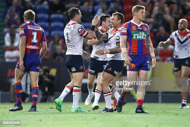 Roosters players celebrate a try during the round seven NRL match between the Newcastle Knights and the Sydney Roosters at McDonald Jones Stadium on...