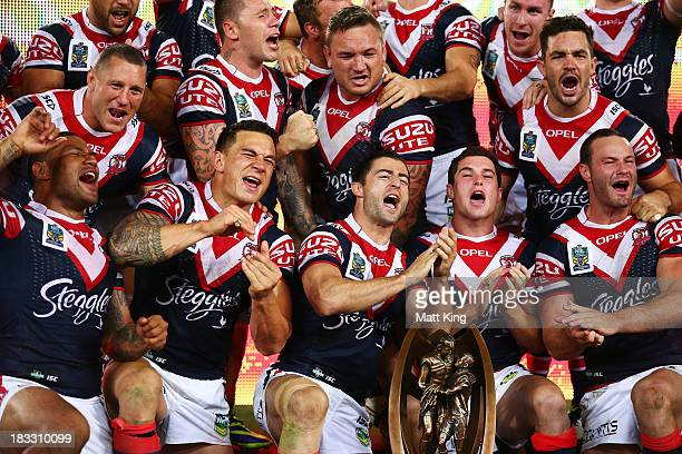 Roosters players celebrate and hold the ProvanSummons Trophy after victory during the 2013 NRL Grand Final match between the Sydney Roosters and the...