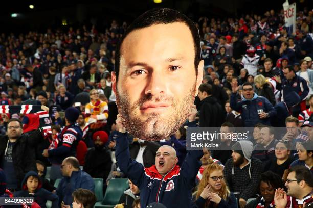 Roosters support cheers as he holds up a Boyd Cordner cut out during the NRL Qualifying Final match between the Sydney Roosters and the Brisbane...