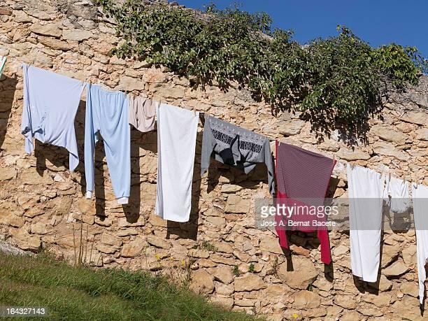 ropa tendida en un muro de piedra - muro stock photos and pictures