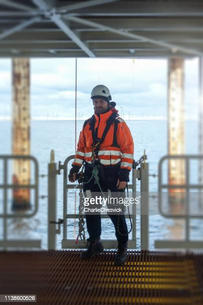 rope access technicia preparing for work on offshore platform in wet-suit - protective sportswear stock pictures, royalty-free photos & images