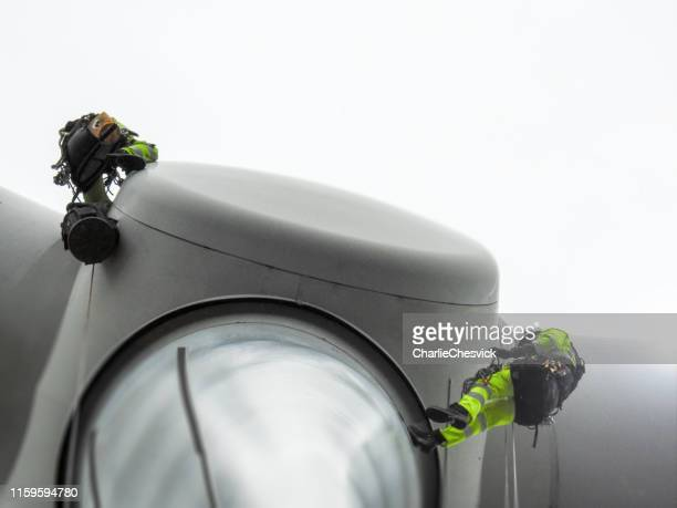 rope access technician doing blade inspection on the tip on wind turbine - high up stock pictures, royalty-free photos & images