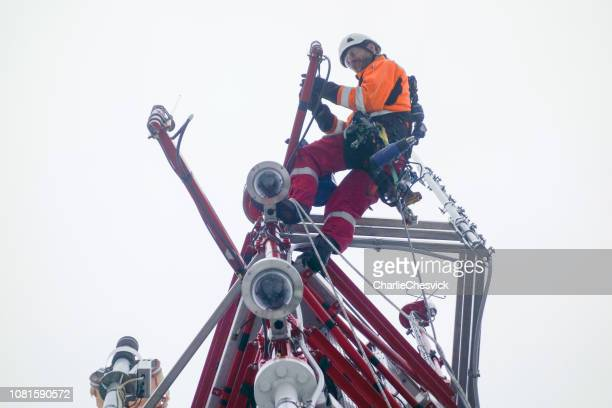rope access technician - electrician - working on top of the tower - antenna and doing inspection - tower stock pictures, royalty-free photos & images